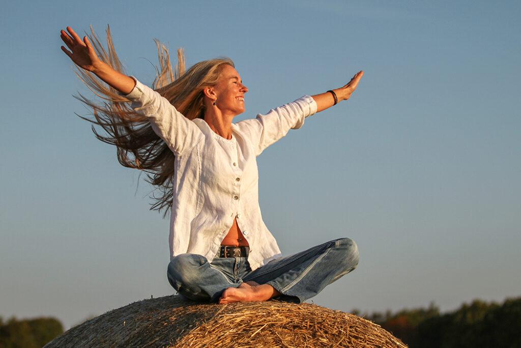 En kvinna sitter på en halmbal i morgonsolen